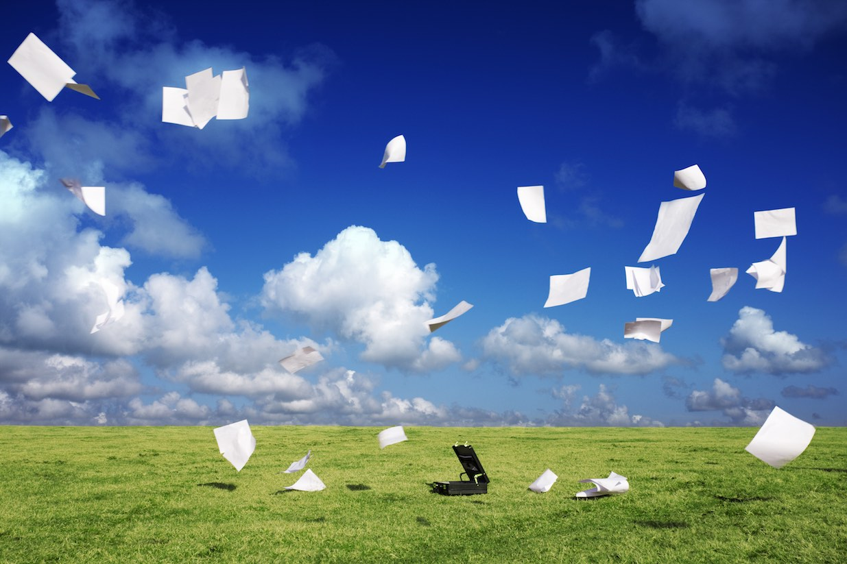Briefcase on windy moorland with paper blowing away